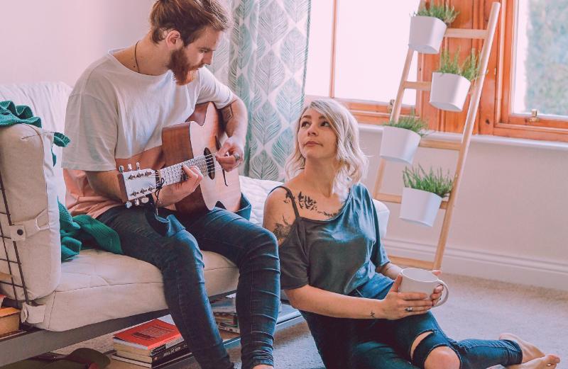 Woman admiring her boyfriend playing guitar
