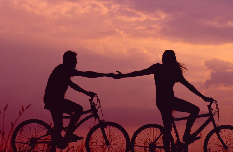Man holding woman's hand on bicycles at sunset