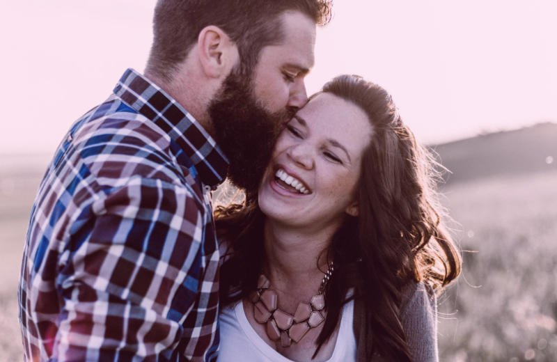 Man passionately kissing woman on her cheek