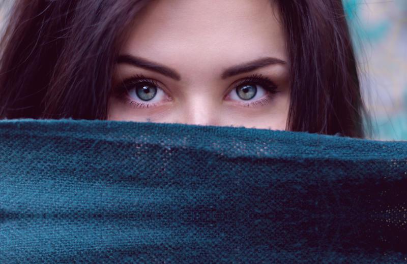 Woman hiding behind scarf
