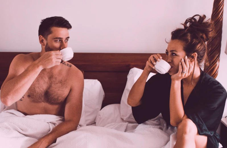 Couple in bed awkwardly looking at each other drinking coffee