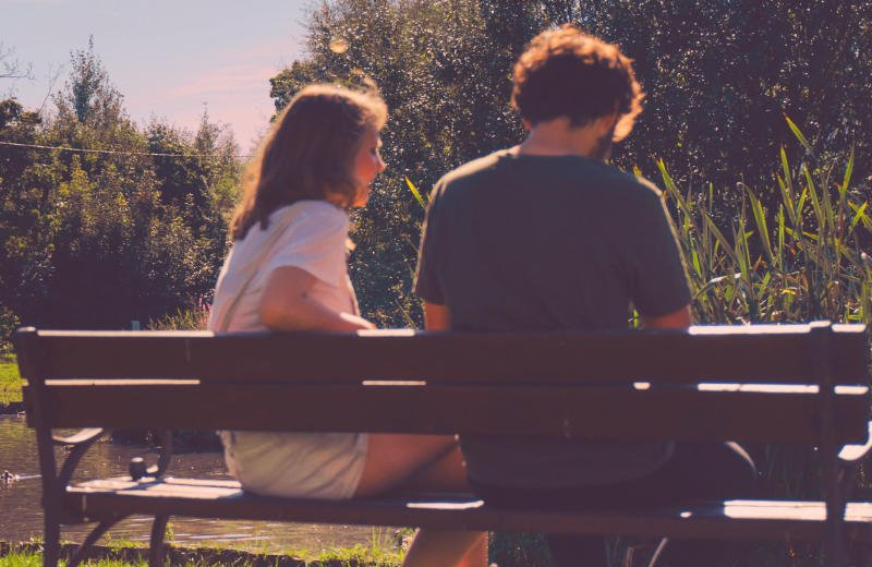 Couple arguing on bench in park