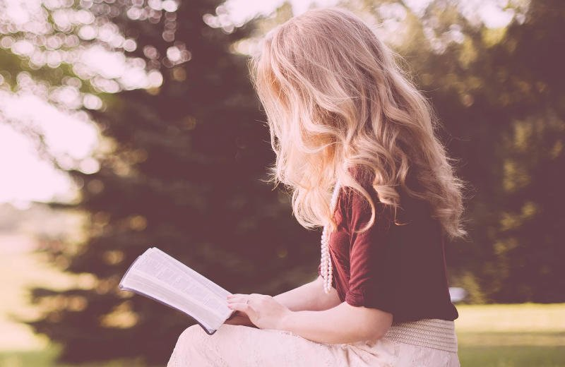 Blond woman reading book