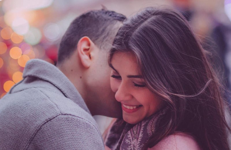 Man kissing giggling woman on her cheek