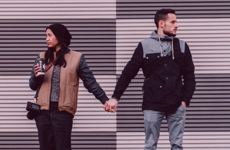 Woman and man holding hands but looking away from each other