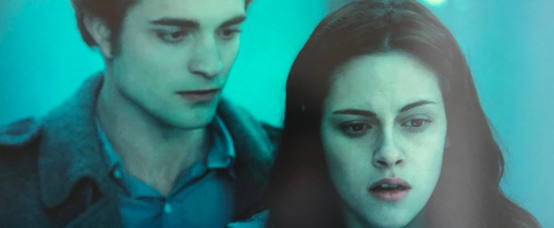 From the movie Twilight, Edward stands behind Bella in the forest in their love-hate relationship.